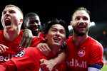 Salzburg's Takumi Minamino, center, jubilates with teammates after scoring his sides second goal during a Champions League group E soccer match between Genk and Salzburg at the KRC Genk Arena in Genk, Belgium, Wednesday, Nov. 27, 2019. (AP Photo/Francisco Seco)