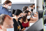 FILE - In this Thursday, Aug. 13, 2020 file photo students of the Robert-Koch vocational college get advise by their teacher, wearing face masks in the classroom, during computer science lessons in Dortmund, Germany. The German government on Wednesday agreed on a strategy to boost the use of data for commercial purposes and signed a deal with state education authorities to fund laptops for teachers who have to work from home because of the virus lockdown. (AP Photo/Martin Meissner, file)