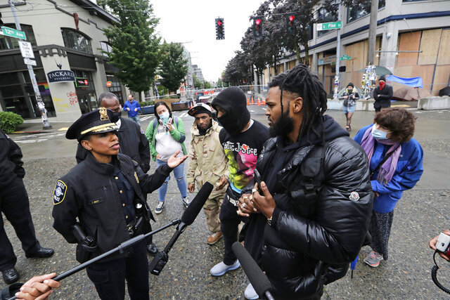 Seattle Police Chief Carmen Best, left, talks with activist Raz Simone, right front, and others near a plywood-covered and closed Seattle police precinct behind them Tuesday, June 9, 2020, in Seattle, following protests over the death of George Floyd, a black man who was in police custody in Minneapolis. Under pressure from city councilors, protesters and dozens of other elected leaders who have demanded that officers dial back their tactics, the police department on Monday removed barricades near its East Precinct building in the Capitol Hill neighborhood, where protesters and riot squads had faced off nightly. Protesters were allowed to march and demonstrate in front of the building, and the night remained peaceful. (AP Photo/Elaine Thompson)