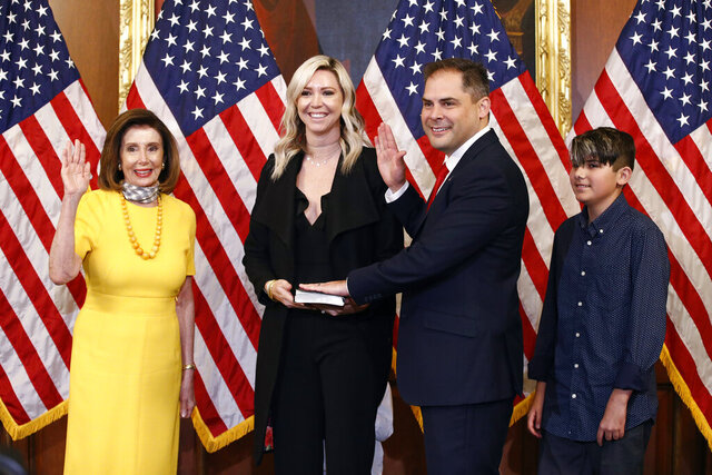 House Speaker Nancy Pelosi of Calif., left, conducts a ceremonial swearing-in for Rep. Mike Garcia, R-Calif., second from right, joined by his wife Rebecca and son Preston, on Capitol Hill in Washington, Tuesday, May 19, 2020. (AP Photo/Patrick Semansky)