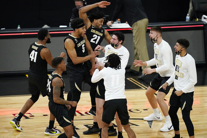 Colorado players celebrate after defeating Southern California in an NCAA college basketball game in the semifinal round of the Pac-12 men's tournament Friday, March 12, 2021, in Las Vegas. (AP Photo/John Locher)