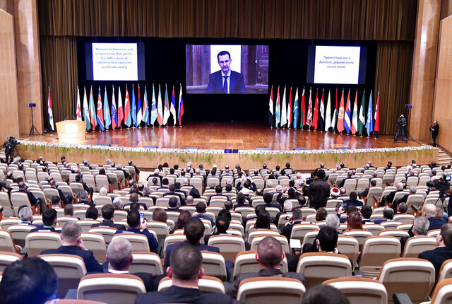 CORRECTS DATE TO NOV. 11, 2020 -- This photo released by the Syrian official news agency SANA, shows Syrian President Bashar Assad virtually addressing the opening session of a two-day international conference on the return of refugees to Syria, organized by Russia, in Damascus, Syria, Wednesday, Nov. 11, 2020. The Syrian government is working to secure the return of millions of refugees who fled war in their country, but Western sanctions are hindering the work of state institutions, complicating those plans, Assad said Wednesday. (SANA via AP)