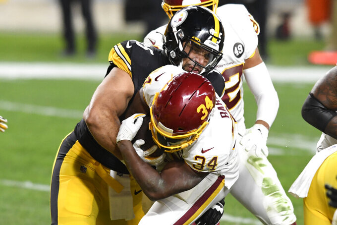 Washington Football Team running back Peyton Barber (34) scores on a 1-yard touchdown run with Pittsburgh Steelers defensive end Lavon Hooks (95) defending during the second half of an NFL football game against the Pittsburgh Steelers in Pittsburgh, Monday, Dec. 7, 2020. (AP Photo/Barry Reeger)