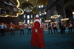 A man draped in a Turkish flag, stands as people walk inside the Byzantine-era Hagia Sophia following the inaugural Friday prayers, in the historic Sultanahmet district of Istanbul, Friday, July 24, 2020. Worshipers held the first Muslim prayers in 86 years inside the Istanbul landmark that served as one of Christendom's most significant cathedrals, a mosque and a museum before its conversion back into a Muslim place of worship. The conversion of the edifice, has led to an international outcry. (AP Photo/Yasin Akgul)
