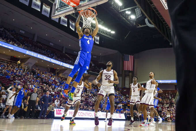 Kentucky forward Nick Richards (4) dunks over Texas A&M forward Josh Nebo (32) during the first half of an NCAA college basketball game Tuesday, Feb. 25, 2020, in College Station, Texas. (AP Photo/Sam Craft)
