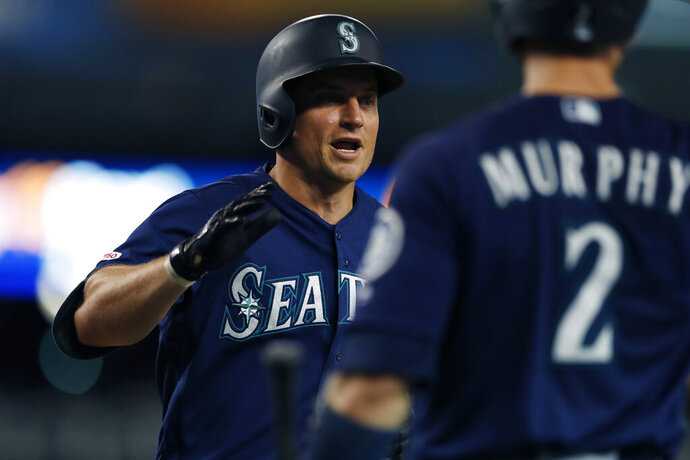 Seattle Mariners' Kyle Seager is greeted at the dugout by teammate Tom Murphy after a three-run home run during the sixth inning of a baseball game against the Detroit Tigers, Tuesday, Aug. 13, 2019, in Detroit. (AP Photo/Carlos Osorio)