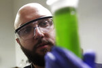 In this Friday, Aug. 16, 2019, photo, chemist David Dawson holds up a vial of extracted cannabis with an organic solvent as he demonstrates testing for THC and other chemicals at CW Analytical Laboratories in Oakland, Calif. Chemists are trying to solve a scientific mystery involving marijuana brownies. Chocolate seems to throw off test results for potency. That could be dangerous for consumers looking to relax, not hallucinate. (AP Photo/Jeff Chiu)