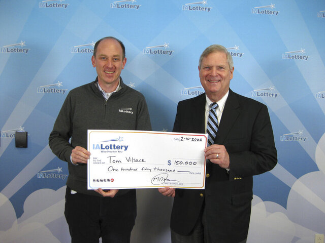 This handout photo provided by the Iowa Lottery shows Iowa Lottery CEO Matt Strawn, left, posing with Tom Vilsack, former Iowa governor and U.S. agriculture secretary, after Vilsack claimed a $150,000 Powerball prize on Monday, Feb. 10, 2020, in Clive, Iowa. Vilsack's ticket matched the Jan. 22, 2020, Powerball number and four of the remaining five numbers. He just missed out on the estimated $347 million jackpot. (AP Photo/Iowa Lottery via AP)