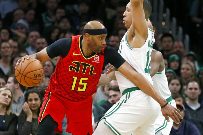 Atlanta Hawks' Vince Carter (15) drives against Boston Celtics' Grant Williams (12) during the first half of an NBA basketball game Friday, Feb. 7, 2020, in Boston. (AP Photo/Mary Schwalm)