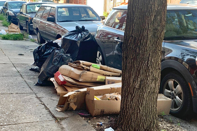 Trash rests piled up on a street Tuesday, July 28, 2020, in the Kensington neighborhood of Philadelphia. The COVID-19 pandemic has frustrated efforts to keep Philadelphia's streets clear of garbage this summer. Residents complain about the stink and the flies. (Kara Kneidl via AP)