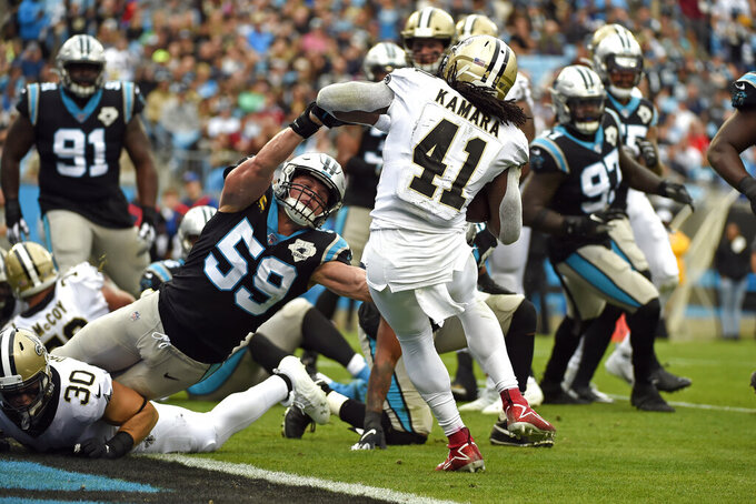 Carolina Panthers middle linebacker Luke Kuechly (59) reaches as New Orleans Saints running back Alvin Kamara (41) scores a touchdown during the first half of an NFL football game in Charlotte, N.C., Sunday, Dec. 29, 2019. (AP Photo/Mike McCarn)