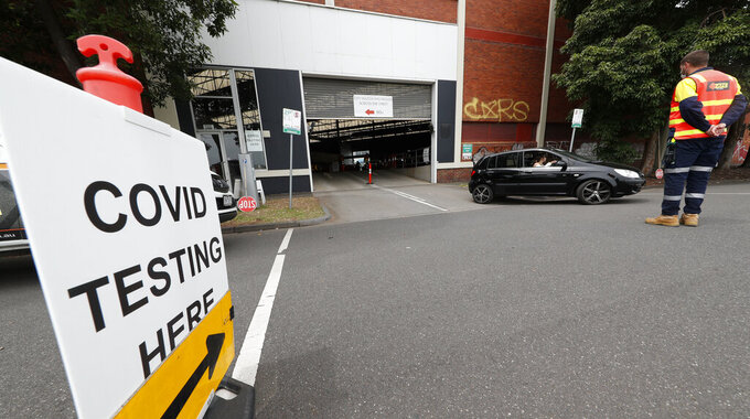 A car leaves a COVD-19 testing station in Melbourne, Australia, Thursday, Feb. 4, 2021. All competition at six Australian Open tuneup events scheduled for Thursday was called off after a worker at one of the tournaments' Melbourne quarantine hotels tested positive for COVID-19.(AP Photo/Hamish Blair)