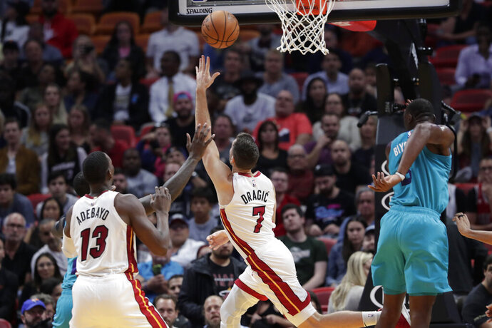 Miami Heat guard Goran Dragic (7) shoots past Charlotte Hornets center Bismack Biyombo, right, during the first half of an NBA basketball game, Monday, Nov. 25, 2019, in Miami. (AP Photo/Lynne Sladky)