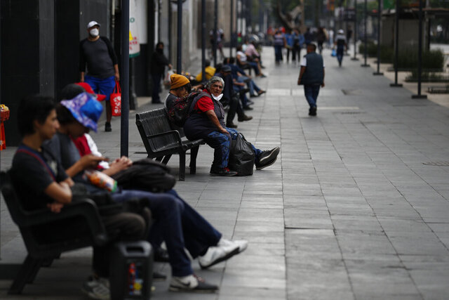 People enjoy the fresh air on benches along Juarez Avenue in central Mexico City, Sunday, May 31, 2020. Mexico's capital plans to reopen certain sectors of the economy and public life beginning Monday, despite the city still being in the most serious