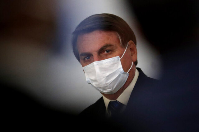 Brazil's President Jair Bolsonaro wearing a mask attends a ceremony about the extension of emergency aid to help the poor population affected by the COVID-19 pandemic, at the Planalto Presidential Palace, in Brasilia, Brazil, Tuesday, Sept. 1, 2020. (AP Photo/Eraldo Peres)
