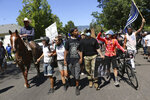 Black Lives Matter protesters are confronted by counter protesters in Minden, Nev. on Saturday, Aug. 8, 2020. Some Black Lives Matter supporters continued to protest after others cut short their participation in a demonstration outside the office of a northern Nevada sheriff and left amid jeers from a larger crowd of counter-protesters. Officials reported no injuries, arrests or damage as social media accounts emerged Monday, Aug. 10, 2020, about a weekend Black Lives Matter protest that was met in a small northern Nevada town by a far larger group of counter-demonstrators, including some bearing military-style weapons and tactical gear. (Jason Bean/Reno Gazette Journal via AP)
