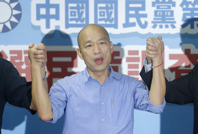 Kaohsiung city mayor Han Kuo-yu raises hands during a media conference after winning the candidacy of the opposition of the Nationalist Party (KMT) for the upcoming presidential elections at the party headquarters, Monday, July 15, 2019, in Taipei, Taiwan. (AP Photo/Chiang Ying-ying)
