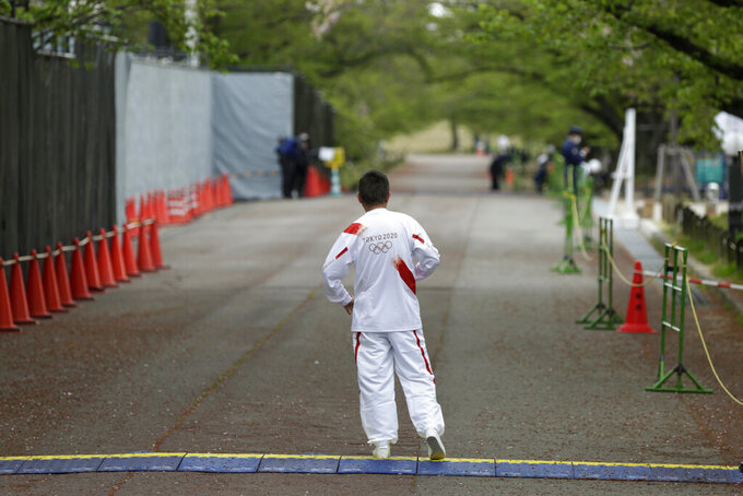 Entertainer Katsura Bunshi IV, participating as an Olympic torch relay runner, waits for his preceding runner during the first day of the Osaka round at a former Expo site in Suita, north of Osaka, western Japan, Tuesday, April 13, 2021. The heavily sponsored torch relay with 10,000 runners crisscrossing Japan also presents hazards. Legs scheduled for Osaka this week were pulled from the streets because of surging COVID-19 cases and relocated into a city park - with no fans allowed. Other legs across Japan are also sure to be disrupted. (AP Photo/Hiro Komae)