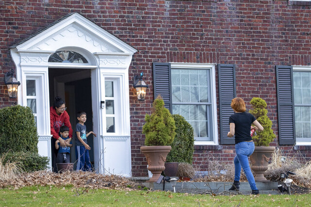 Nanny Lina Cedeno, right, keeps her distance from the front door as she picks up her paycheck and a gift from the children she cares for made for her, Friday, March 20, 2020, in Montclair, N.J. Cedeno hasn't worked for the family in a week because of the coronavirus fears. (AP Photo/Mary Altaffer)