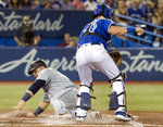 Seattle Mariners' Daniel Vogelbach, left, scores as Toronto Blue Jays catcher Reese McGuire catches a late throw to the plate during fourth-inning baseball game action in Toronto, Saturday, Aug. 17, 2019. (Fred Thornhill/The Canadian Press via AP)