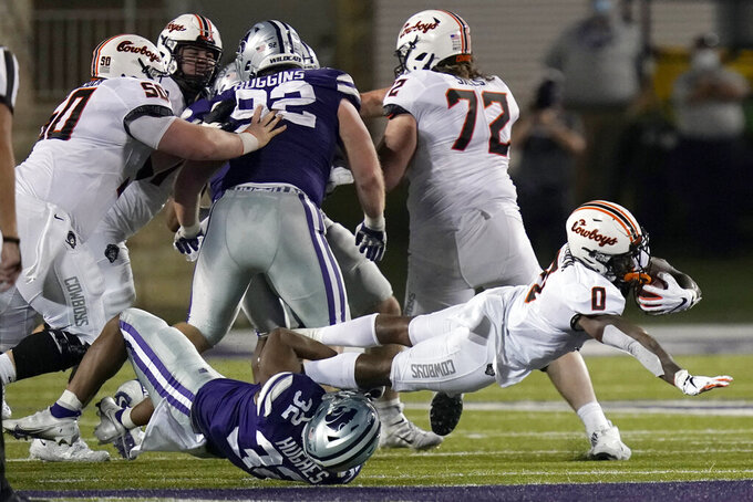 Oklahoma State running back LD Brown (0) is tackled by Kansas State linebacker Justin Hughes (32) during the second half of an NCAA college football game in Manhattan, Kan., Saturday, Nov. 7, 2020. (AP Photo/Orlin Wagner)