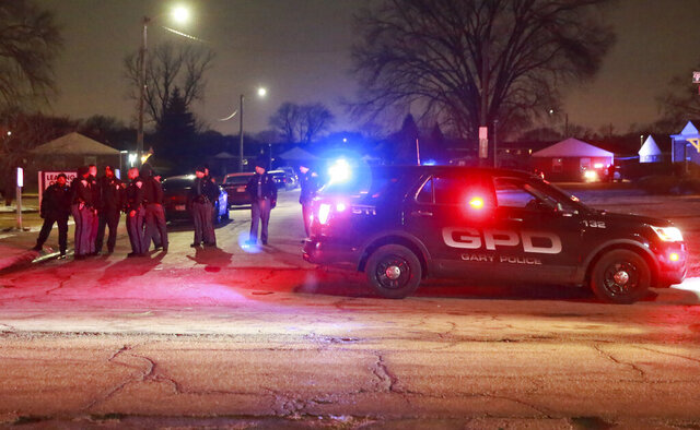 Gary and Indiana State Police officer stand at the entrance to the Westbrook Apartments where Gary police officers were wounded in a shooting incident Monday evening, Jan. 13, 2020 in Gary, Ind. One of the officers returned fire killing the suspect.  (John J. Watkins/The Times via AP)