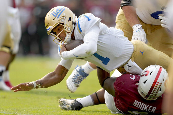 UCLA quarterback Dorian Thompson-Robinson (1) dives for a first down over Stanford defensive end Thomas Booker, bottom right, during the first half of an NCAA college football game Saturday, Sept. 25, 2021, in Stanford, Calif. (AP Photo/Tony Avelar)