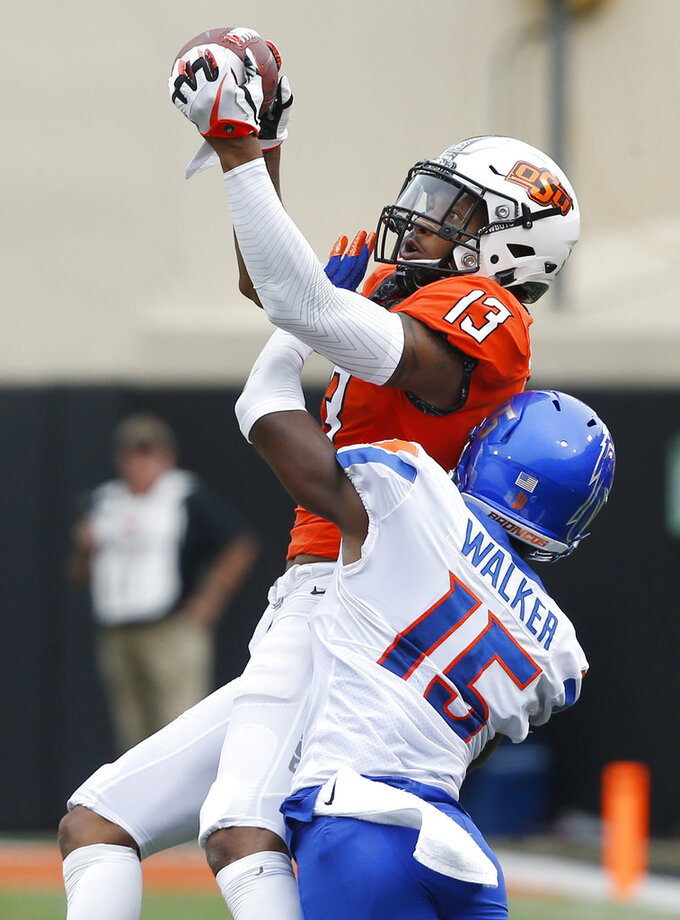 Oklahoma State wide receiver Tyron Johnson (13) catches a pass defended by Boise State cornerback Jalen Walker (15) in the first half of an NCAA college football game in Stillwater, Okla., Saturday, Sept. 15, 2018. (AP Photo/Sue Ogrocki)