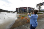Michelle Harper of Masontown, Pa. takes a photo of water flooding the vendor area as races for both the Truck Series and NASCAR Cup Series auto race were postponed due to inclement weather at Bristol Motor Speedway, Sunday, March 28, 2021, in Bristol, Tenn. (AP Photo/Wade Payne)
