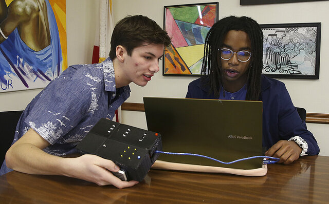 Alex Johnson, left, and Jonathan Walker operate a device they invented that turns text into braille on Thursday, Feb. 13, 2020 in Panama City, Fla. The two high school students submitted their device with a video presentation to the national Invention Convention and were awarded the opportunity to receive a patent. (Patti Blake/News Herald via AP)