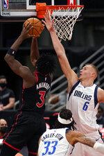 Dallas Mavericks forward Kristaps Porzingis (6) blocks a shot by Toronto Raptors forward OG Anunoby (3) during the second half of an NBA basketball game Monday, Jan. 18, 2021, in Tampa, Fla. (AP Photo/Chris O'Meara)