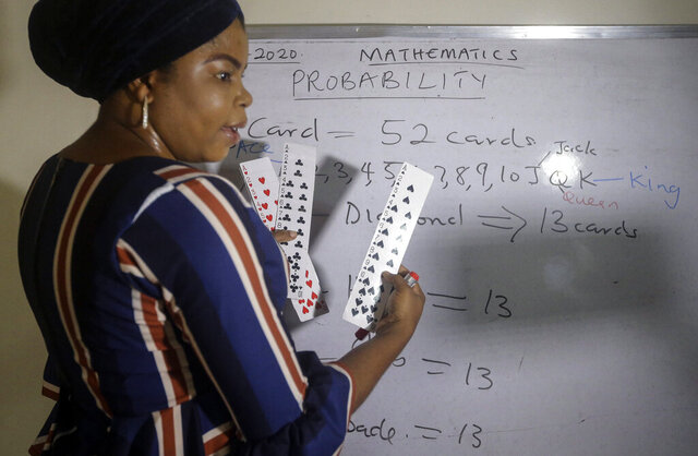 Mathematics teacher Basirat Olamide Ajayi, 36, teaches probability theory with the aid of playing cards, online via her mobile phone from her house in Lagos, Nigeria Saturday, Aug. 15, 2020. The teacher from a Lagos public school is helping students across the country, and internationally, learn math virtually during coronavirus restrictions that have prevented most children from returning to class in Nigeria. (AP Photo/Sunday Alamba)