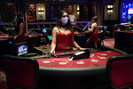 A dealer wearing a protective face mask waits for customers before the reopening of the D Las Vegas hotel and casino, Wednesday, June 3, 2020, in Las Vegas. Casinos were allowed to reopen on Thursday after temporary closures as a precaution against the coronavirus. (AP Photo/John Locher)