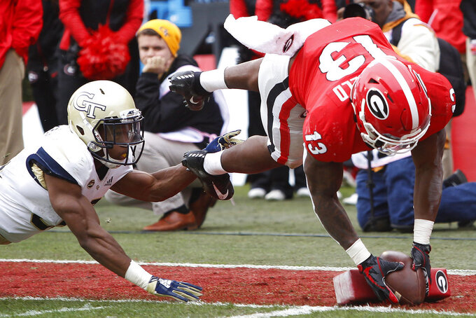 Georgia tailback Elijah Holyfield (13) drives over the goal line past Georgia Tech defensive back Jaytlin Askew (33) for a touchdown in the first half of an NCAA college football game Saturday, Nov. 24, 2018, in Athens, Ga. (Joshua L. Jones/Athens Banner-Herald via AP)