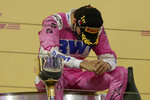 Racing Point driver Sergio Perez of Mexico takes a moment on the podium after wining the Formula One Bahrain Grand Prix in Sakhir, Bahrain, Sunday, Dec. 6, 2020. (Tolga Bozoglu, Pool via AP)