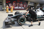 Mercedes crew push the car of Lewis Hamilton past promotional board for the Chinese Formula One Grand Prix at the Shanghai International Circuit in Shanghai on Friday, April 12, 2019. (AP Photo/Ng Han Guan)