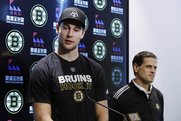 Boston Bruins defenseman Brandon Carlo speaks, as General Manager Don Sweeney listens during a news conference at the hockey team's practice facility, Tuesday, Sept. 17, 2019, in Boston. The Bruins have signed Carlo to a two-year contract with an annual NHL cap hit of $2.85 million. Carlo, 22, skated in 72 games with the Bruins in 2018-19. (AP Photo/Elise Amendola)