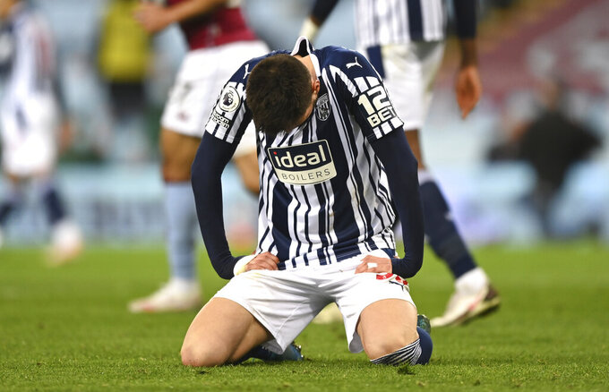 West Bromwich Albion's Okay Yokuslu sits on the pitch in dejection at the end of the English Premier League soccer match between Aston Villa and West Bromwich Albion at Villa Park Stadium in Birmingham, England, Sunday, April 25, 2021. (Shaun Botterill/Pool via AP)