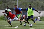 In this Saturday, May 4, 2019, Francis Kalombo from Congo, right, controls the ball during a friendly match between African team and Afghan migrants at a soccer field, in Moria village, on the northeastern Aegean island of Lesbos, Greece. A 10-minute walk from Europe's largest refugee camp is a place where residents of the Moria camp on the Greek island of Lesbos can briefly forget about their tiny container-homes and crowded tents and instead worry about corner kicks and throw-ins. Many of the players hope to turn professional and leave the camp, where they are forced to remain indefinitely under European Union rules designed to limit the number of migrants and refugees reaching the mainland. (AP Photo/Thanassis Stavrakis)