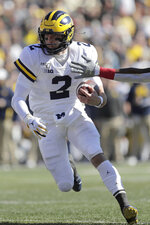Michigan quarterback Shea Patterson runs with the ball against Maryland during the first half of an NCAA college football game, Saturday, Nov. 2, 2019, in College Park, Md. (AP Photo/Julio Cortez)