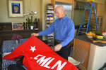 """In this Jan. 17, 2019 photo, Todd Greentree, a former U.S. Embassy political officer in El Salvador during its civil war, shows a rebel Farabundo Marti National Liberation Front flag in his Santa Fe, N.M., home as he talks about the killings of four Dutch journalists in 1982. Greentree said that he's """"very ambivalent"""" about seeking justice for what he called an obvious war crime. (AP Photo/Russell Contreras)"""