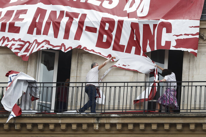 Residents of a building cut up a banner which was lowered from the roof of his building by far-right protestors with the Identitarian nationalist French movement during a march against police brutality and racism in Paris, France, Saturday, June 13, 2020, organized by supporters of Adama Traore, who died in police custody in 2016 in circumstances that remain unclear despite four years of back-and-forth autopsies. The march is expected to be the biggest of several demonstrations Saturday inspired by the Black Lives Matter movement in the U.S., and French police ordered the closure of freshly reopened restaurants and shops along the route fearing possible violence. (AP Photo/Thibault Camus)