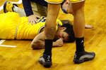 Michigan guard Eli Brooks is examined after a play during the first half of an NCAA college basketball game against Michigan State, Sunday, March 7, 2021, in East Lansing, Mich. (AP Photo/Carlos Osorio)