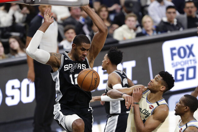 San Antonio Spurs center LaMarcus Aldridge (12) scores over Milwaukee Bucks forward Thanasis Antetokounmpo, second from right, during the second half of an NBA basketball game in San Antonio, Monday, Jan. 6, 2020. (AP Photo/Eric Gay)