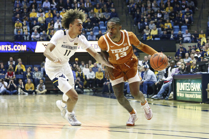 Texas guard Jase Febres (13) drives it up court as he is defended by West Virginia forward Derek Culver (1) during the first half of an NCAA college basketball game Monday, Jan. 20, 2020, in Morgantown, W.Va. (AP Photo/Kathleen Batten)