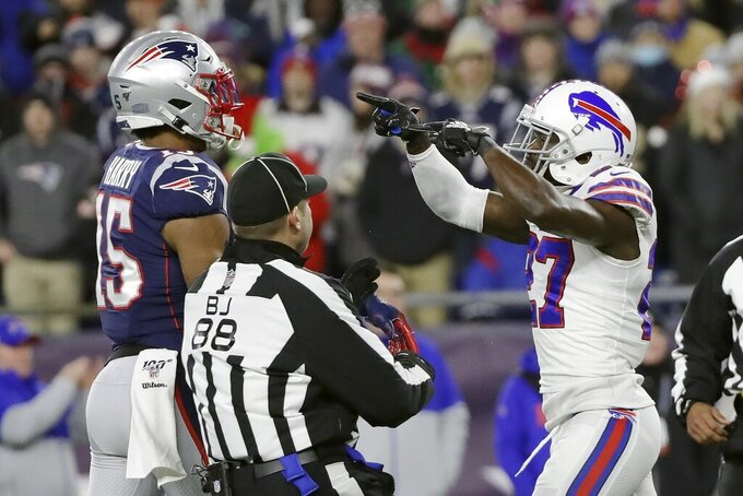 Back judge Brad Freeman, center, intervenes as New England Patriots wide receiver N'Keal Harry, left, and Buffalo Bills cornerback Tre'Davious White, right, face off after a play in the first half of an NFL football game, Saturday, Dec. 21, 2019, in Foxborough, Mass. (AP Photo/Elise Amendola)