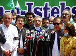 Pakistan's President Arif Alvi, center, stands with parliamentarians while addressing participants at a rally to show solidarity with Kashmiri people on the eve of the first anniversary of India's decision to revoke the disputed region's semi-autonomy, in Islamabad, Pakistan, Wednesday, Aug. 5, 2020. Last year on Aug. 5, India's Hindu-nationalist-led government of Prime Minister Narendra Modi stripped Jammu and Kashmir's statehood, scrapped its separate constitution and removed inherited protections on land and jobs. (AP Photo/A.H. Chuadary)