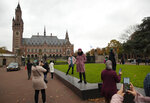 Tourists take pictures of the Peace Palace, rear, which houses the International Court in The Hague, Netherlands, Monday, Nov. 11, 2019, where Gambia filed a case at the United Nations' highest court accusing Myanmar of genocide in its campaign against the Rohingya Muslim minority. A statement released Monday by lawyers for Gambia says the case also asks the International Court of Justice to order measures
