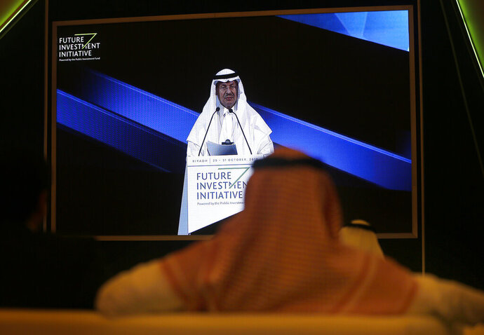 Participants watch Saudi Energy Minister Prince Abdulaziz bin Salman on a screen during his speech at the Future Investment Initiative forum in Riyadh, Saudi Arabia, Wednesday, Oct. 30, 2019. The long-planned initial public offering of a sliver of Saudi Arabia's state-run oil giant Saudi Aramco will see shares traded on Riyadh's stock exchange in December, a Saudi-owned satellite news channel reported Tuesday as the kingdom's marquee investment forum got underway. (AP Photo/Amr Nabil)