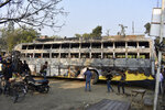 People look at the charred remains of a bus that caught fire after ramming into a truck in Kannauj, in the northern Indian state of Uttar Pradesh, Saturday, Jan. 11, 2020. At least 20 people died when in the accident, police said. Another 21 people were taken to a hospital, some of them in critical condition, following the crash late Friday, said senior police officer Mohit Aggarwal. (AP Photo)